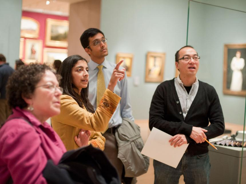 Visitors looking at painting in Gallery 226, person at center pointing