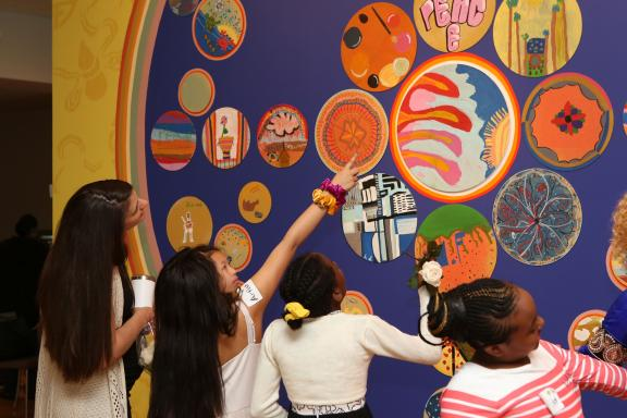 Children looking and pointing at circular mandala paintings on the wall.