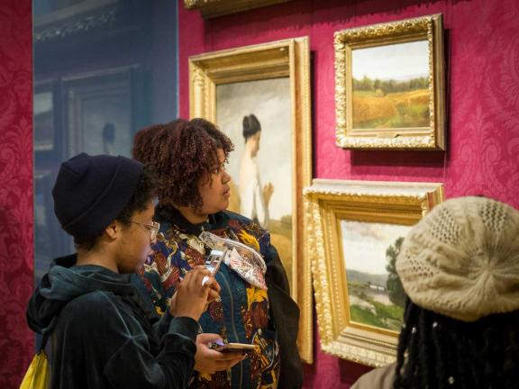 Two visitors holding smartphones looking at paintings in Salon gallery