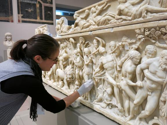 Conservator stabilizing and cleaning a Roman marble sarcophagus