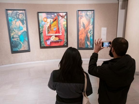 Two visitors looking at three paintings hanging in rotunda gallery
