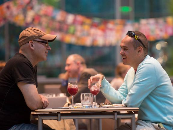 Two diners sitting at table in New American Cafe each with a glass of sangria