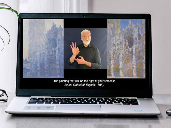 A laptop on a desk showing a still from a virtual ASL program