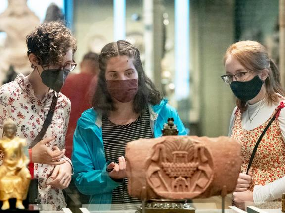 Three visitors wearing face masks looking at sculptures inside case in South and Southeast Asian Art gallery