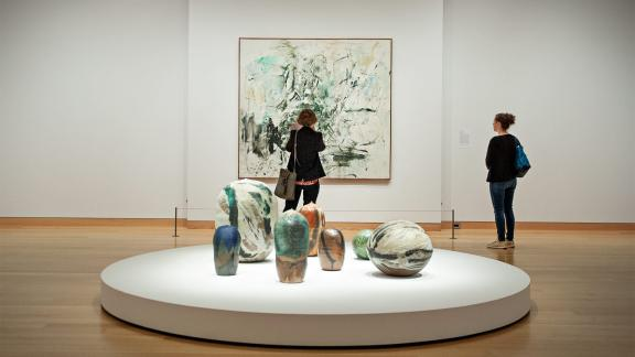 Two visitors looking at painting in Women Take the Floor exhibition, with various shaped ceramic sculptures on platform in foreground