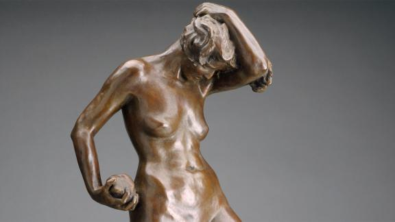 detail of bronze sculpture depicting woman with one arm touching top of head and the other holding stone
