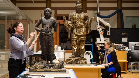Conservators working on Japanese Buddha sculptures