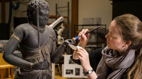 Conservator working on Japanese Buddha sculpture