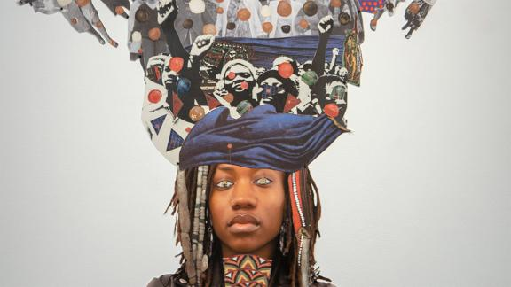 head of woman standing in front of a mixed-media collage depicting many raised fists
