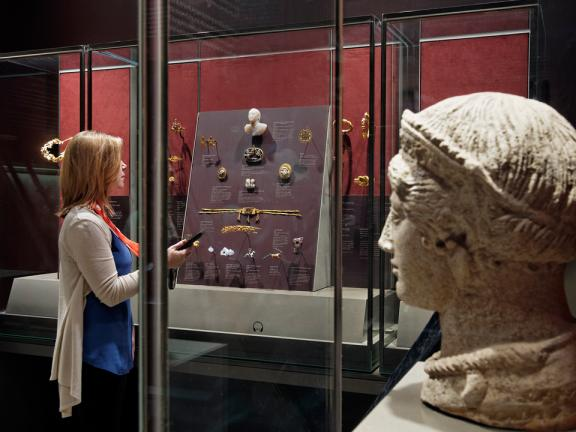 Visitor with multimedia handheld guide looking at ancient jewelry in display case, large sculpture in foreground