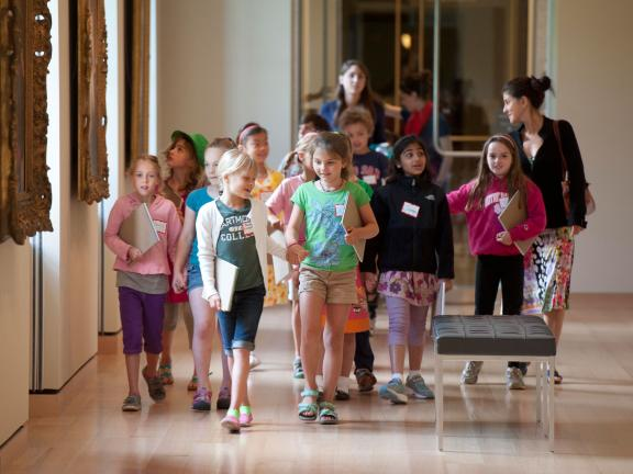 Group of kids with drawing pads walking down British portraiture gallery