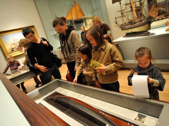 Family looking inside drawer in model ship gallery