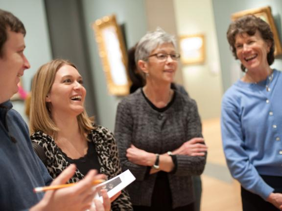 Four visitors looking at gallery wall, smiling