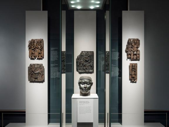 View of Art of Benin Kingdom gallery, with bronze head in foreground and bronze plaques on wall in background