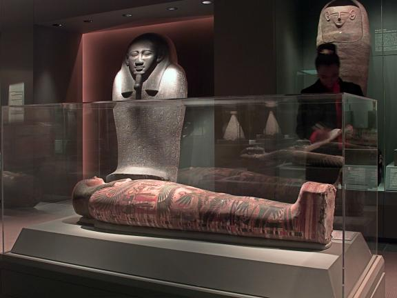 Installation view of the mummies gallery, people looking at mummies