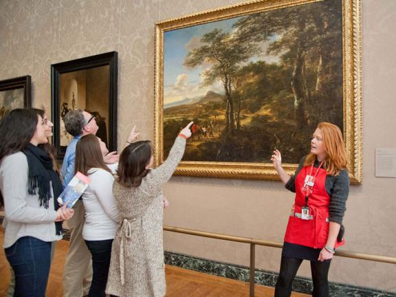 Visitors in tour group pointing at painting, with MFA Ambassador standing in front of painting