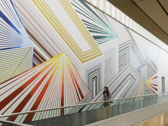 View of large mural, Tread Lightly, featuring angled geometric shapes, on wall in Linde Family Wing