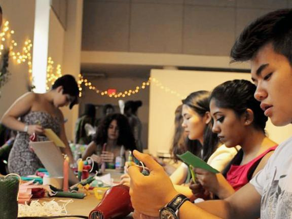 Teens sitting at table working on art project