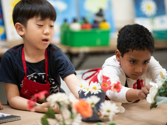 Two kids working on vase filled with flowers